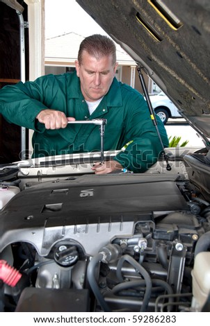 A mechanic works of a car during routine maintenance. - stock photo