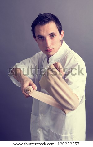 A medic bandaging his left arm - stock photo