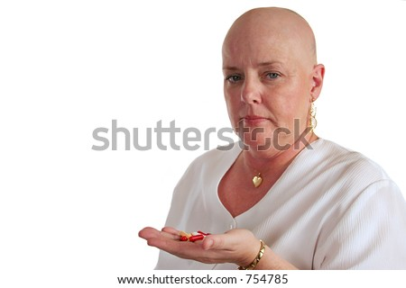 A medical patient holding a handful of pills and looking disgusted she has to take them. - stock photo