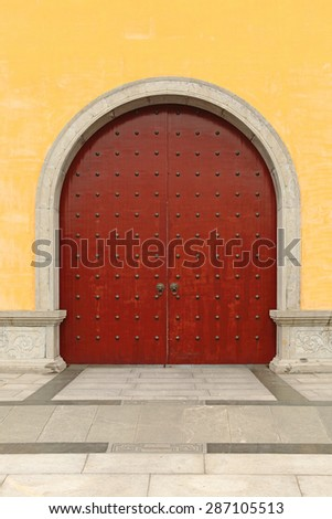 A medieval Chinese city gate on a yellow mason wall. - stock photo