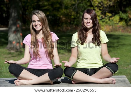 A meditation yoga pose performed by young girls at the park. - stock photo