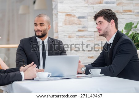 A meeting of the Board. Four smiling successful businesspeople at meeting, sitting at table in office while discussing business matters. - stock photo