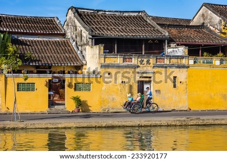 A men cycling cyclos carrying tourists visit the ancient town of Hoi An, Vietnam. - stock photo