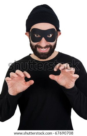 A men with beard dressed as a funny thief (black clothes, black woollen hat, masked eyes) smiling and holding his hands as if ready to steal something while looking straight at camera. - stock photo