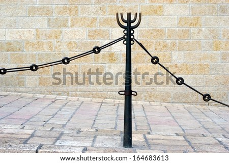 A Menorah icon on a fence in empty street of Jerusalem old city with Jerusalem stone wall in the background. - stock photo