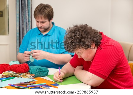 a mentally disabled woman and young man doing arts and crafts - stock photo