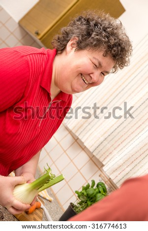 a mentally disabled woman in the kitchen is glad - stock photo