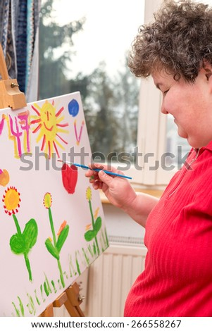 a mentally disabled woman painting a picture - stock photo