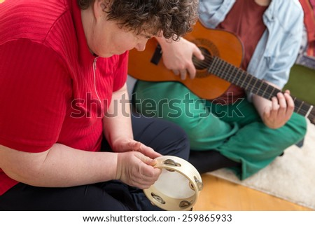 a mentally disabled woman playing a tambourine - stock photo