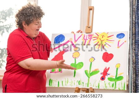 a mentally disabled woman showing her painting - stock photo