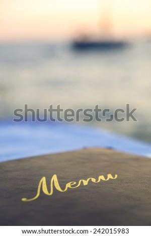 A menu laid on a seafood restaurant table with a boat out of focus on the sea at sunset in the background - stock photo