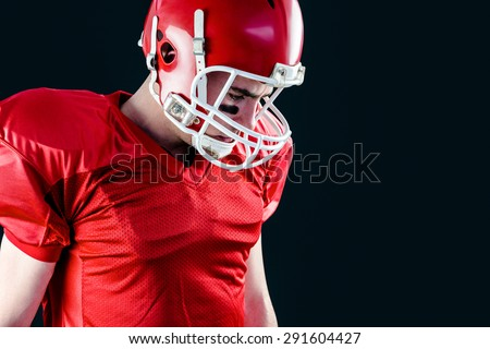 A mercian football player taking his helmet on her head with black background - stock photo