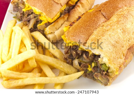 A messy Philly Cheesesteak with onions peppers and mushrooms, fries on the side - stock photo