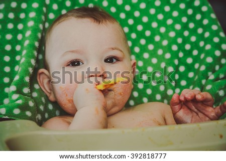 A messy ten month old baby boy sitting in his highchair, chewing on his fork during meal time - stock photo