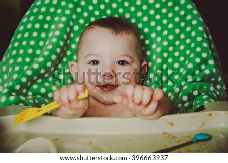 A messy ten month old baby boy sitting in his highchair, playing with his fork during meal time - stock photo