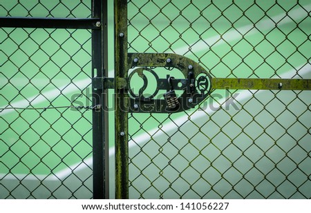 A metal door leading to a tennis court with tennis ball logo on the lock/handle - stock photo