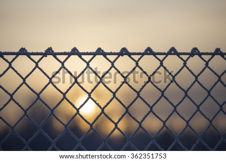 A metal fence against a wintry sunset. Some snow and frost is covering the metal wires.  - stock photo