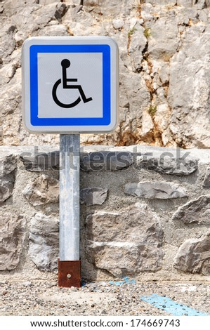 A metal pole with a disabled parking slot sign at a parking place - stock photo