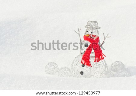 A metal snowman with a red scarf and balls made of silver wire on a backdrop of snow - stock photo