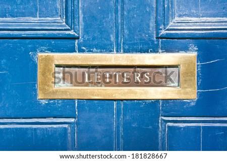 A metallic letterbox in a blue wooden door - stock photo