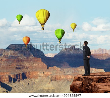 A metaphor of infinity investment opportunity. Businessman is standing on the precipice and looking at balloons. - stock photo