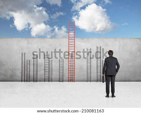 A metaphor of leadership concept. Young businessman is standing in front of the wall with ladders. - stock photo