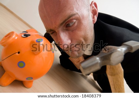 A metaphorical image of a crazy businessman breaking his piggybank to buy a new house from his savings. - stock photo