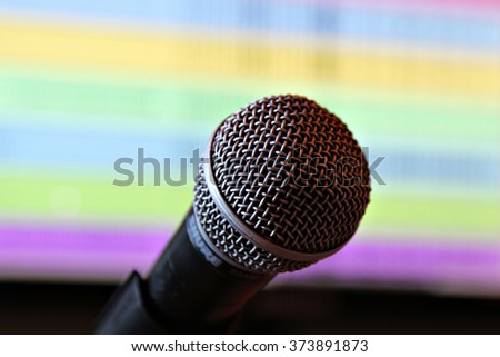 A microphone against a computer screen in a music recording studio. - stock photo