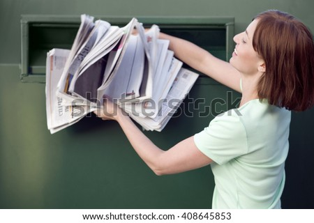 A mid-adult woman recycling paper - stock photo