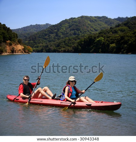 A middle age couple kayaking on the lake - stock photo