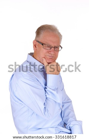 A middle age man in a blue shirt with his hand on his chin, thinking 