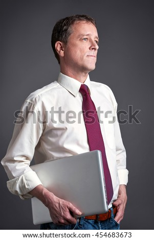 A middle age man standing with a laptop and looking sideways - stock photo