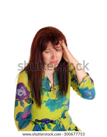 A middle age woman in a colorful dress with her hand on her head, cryingfor the bad headache, isolated for white background. - stock photo
