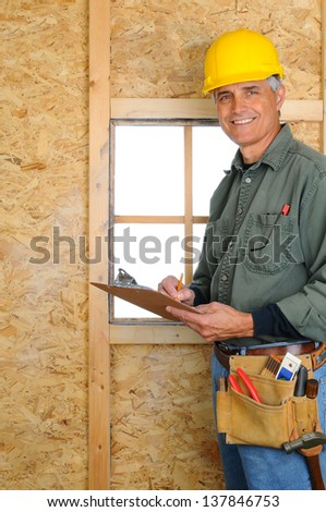 A middle aged contractor standing in new construction writing on a clip board. Man is wearing jeans, work shirt, tool belt and a hard hat, and smiling at the camera. Vertical Format. - stock photo