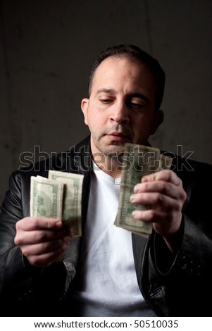 A middle aged man counting a handful of one hundred dollar bills. Shallow depth of field with focus on the face. - stock photo