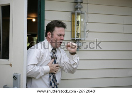 A middle aged man leaving a building and having a coughing fit. - stock photo