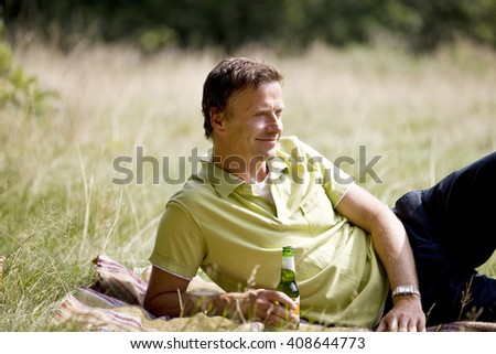 A middle aged man lying on the grass, having a beer - stock photo