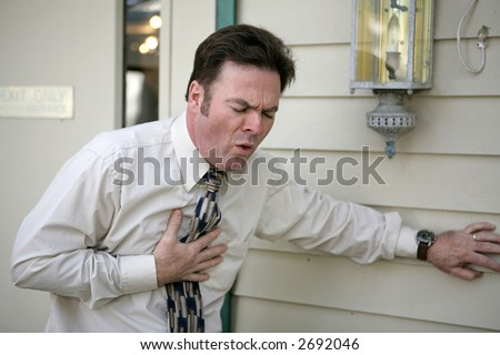 A middle aged man outside his office suffering from a persistent cough. - stock photo