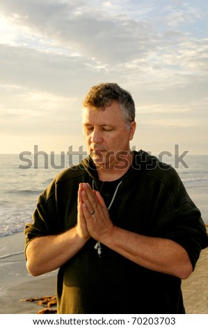A middle-aged man praying at the ocean in evening light. - stock photo