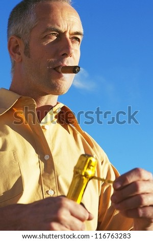 A middle-aged man puffs contentedly on a cigar while opening a bottle of champagne in a sign of wealth and success - stock photo