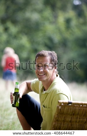 A middle aged man sitting on the grass, drinking a bottle of beer - stock photo