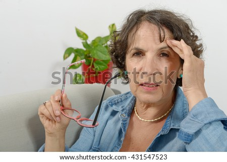 a middle-aged woman has headache - stock photo