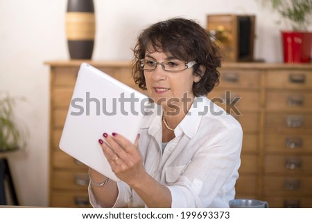 a middle-aged woman using a  computer tablet in her kitchen - stock photo