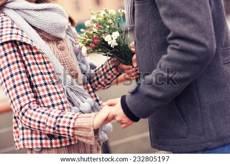 A midsection of a couple holding hands and flowers - stock photo