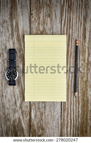a military style watch and a blank notepad with a pencil - stock photo
