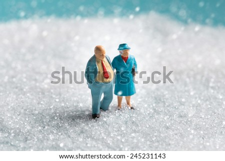 a miniature Senior couple walking on the snow in winter time - stock photo