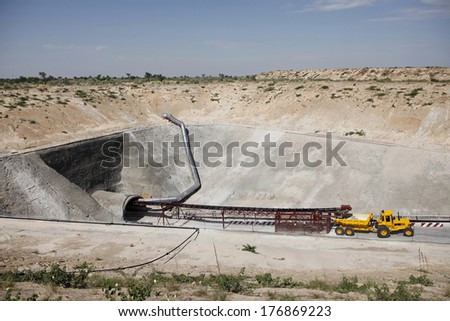 A mining vehicle is parked just outside on the entrance of an inclined diamond mine shaft in the desert - stock photo
