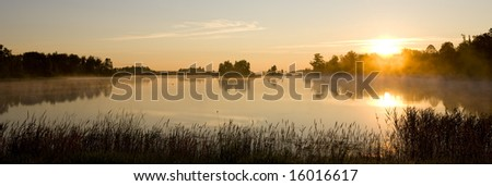 A minnesota morning as mist rolls off a small still lake. - stock photo