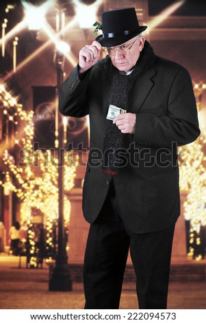 A miserly old man holding onto his top hat while clutching a wad of 100 dollar bills as he walks outside past a Christmas-decorated mall at night. - stock photo