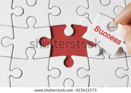 "A missing puzzle with a hand hold a piece of ""Success"" text puzzle want to complete it - business and finance concept - stock photo"